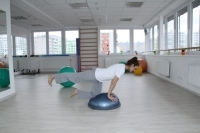 Exercising on a balance device BOSU - stretching legs on all fours